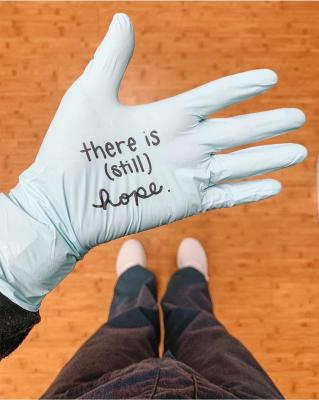 gloved hand with a message written on the palm - 'There is still hope'