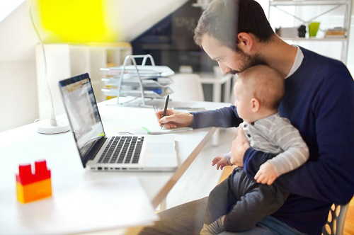 man working from home while holding a baby