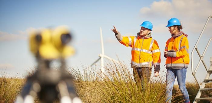 Energy workers walking across a field with wind farm in the background