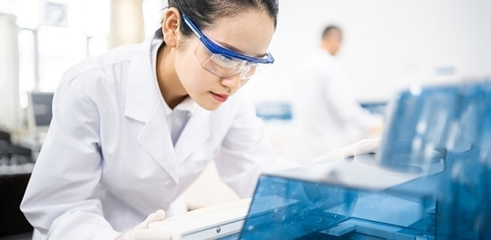 Scientist in white coat and protective glasses at work in a laboratory