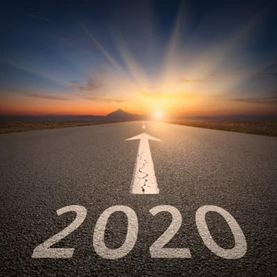2020 in foreground, written on a road with an arrow, pointing to a sunset in the background
