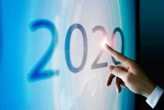 a finger points to 2020 written on a wall
