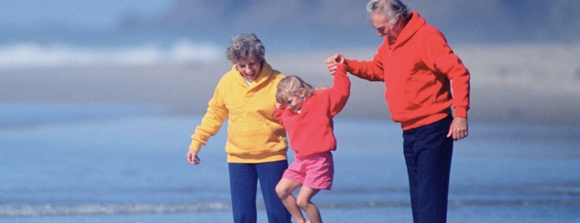 Grandparents hold child's hands and lift her up while walking on beach