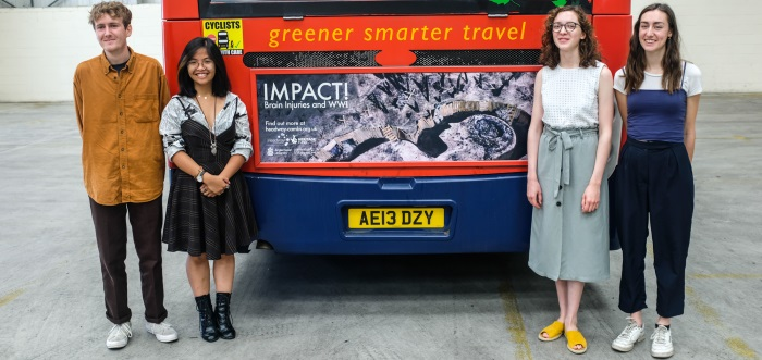 Students standing behind a bus