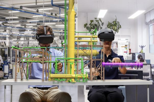 Two men wear augmented reality headsets and work with models _AVEVA Unified Supply Chain