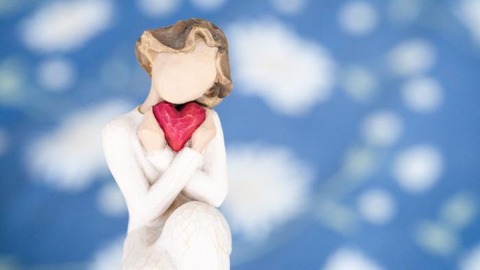faceless 'angel' character holding a heart