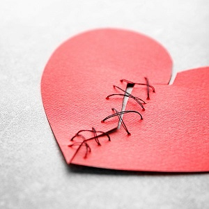 Broken heart depicted  in paper tied together with string_ BHF image