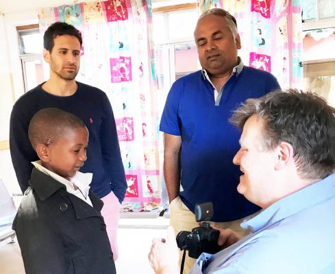 CGHP volunteer surgeon Julian Fraser, now retired, shows his camera to the same young patient