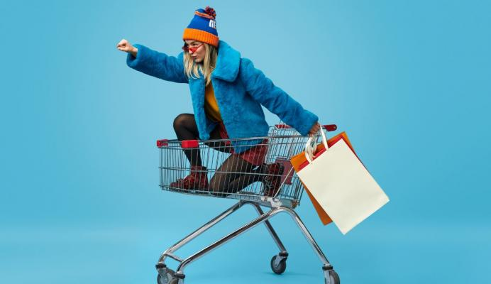Colourfully dressed girl sat in the shopping cart in a power pose