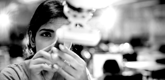 B&W shot of woman looking at a gadget she's holding that's out of focus