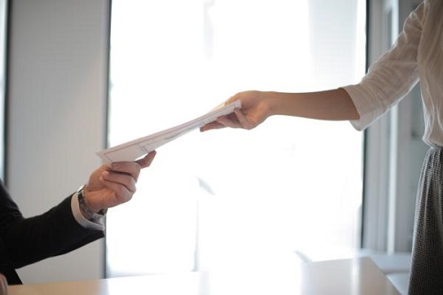 Job applicant hands over her documents/ https://www.canva.com/