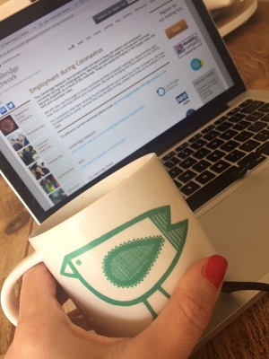 Claire's hand and mug with laptop inthe background