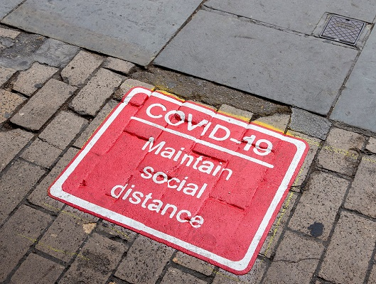 Covid - social distancing sign on pavement