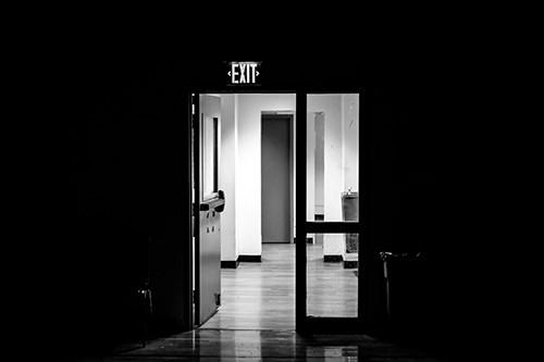 Open door underneath an EXIT sign