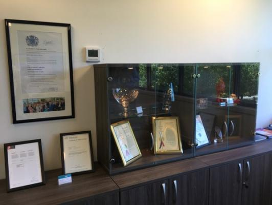 Queens Award Certificate on a wall next to trophy cabinet. Image courtesy of Global Inkjet Systems