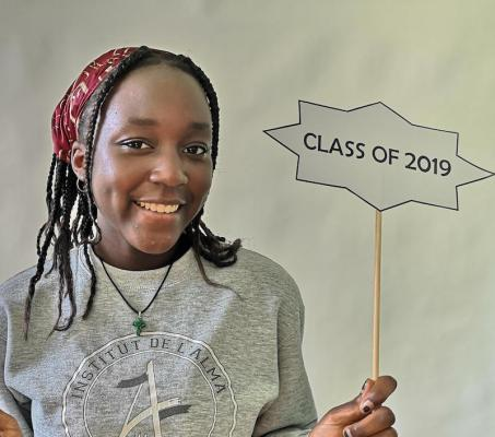 girl holding a Class of 2019 banner