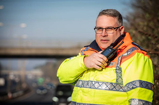 Highways England traffic officer speaking into his Sepura SC20 radio
