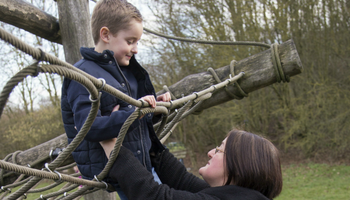 Photo of a young boy and his mother on a park's climbing frame
