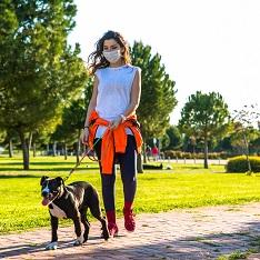 Masked woman walking dog