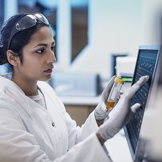 girl in white coat looking at clinical screen