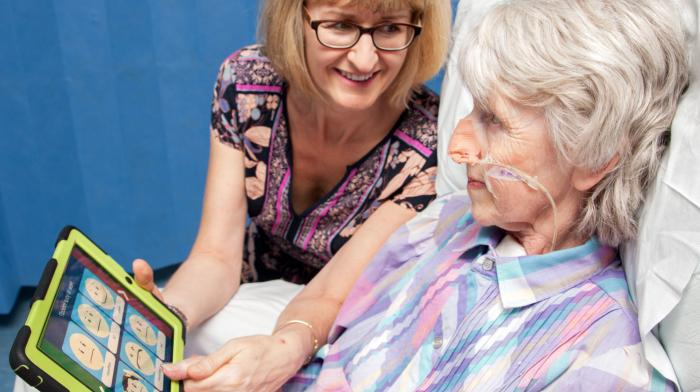 woman patient with helper showing her symbols on a tablet