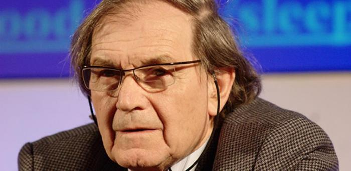 Headshot of Roger Penrose wearing a suit