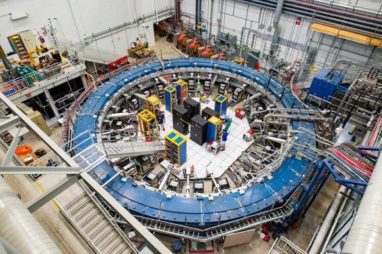 The Muon g-2 ring sits in its detector hall amidst electronics racks, the muon beamline, and other equipment. This impressive experiment operates at negative 450 degrees Fahrenheit and studies the precession (or wobble) of muons as they travel through the magnetic field. Credit: Fermilab/Reidar Hahn