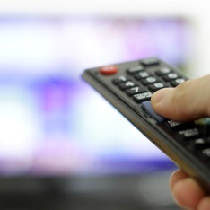 Hand on a TV remote control