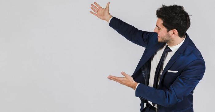 Man pointing at an empty white wall