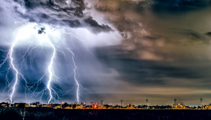thunderstorm and lightning strikes over a town