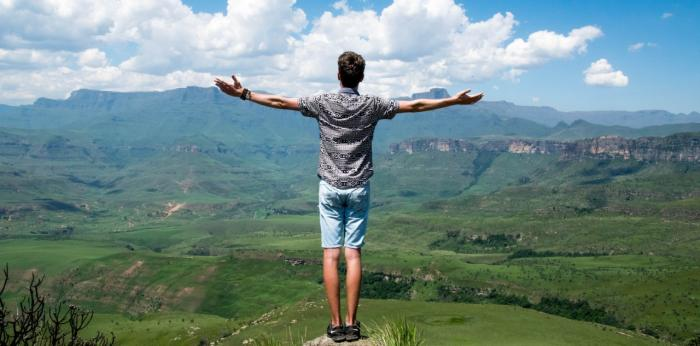 Young man standing on mountaintop with arms open wide across countryside view