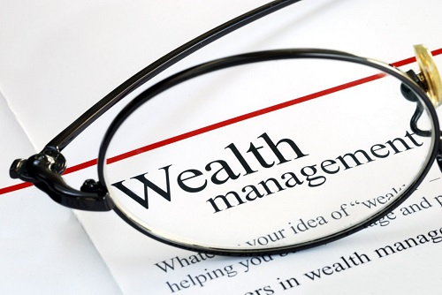 A printed page with the title' Wealth management' visible under a pair of spectacles
