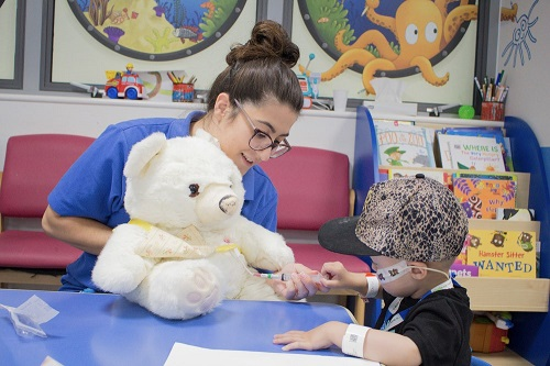 Paediatric day unit healthcare play specialist Gaby Catrisano showing two-year-old Jaymen Woolston Snowy the bear. Snowy is fitted with a Hickman line, which is used for the administration of chemotherapy or other medications, as well as for the withdrawal of blood for analysis.