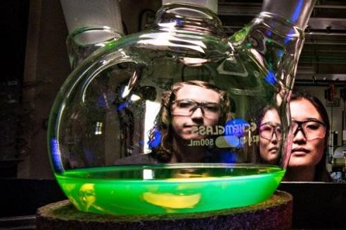 Two women looking at liquid in bottle