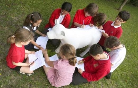 cbildren sitting around a model of a small cow