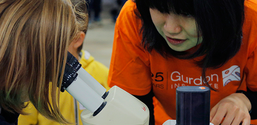 girl looking through microscope watched by woman scientist