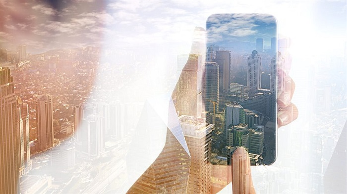 mobile phone in a hand, superimposed over an image of a city skyline