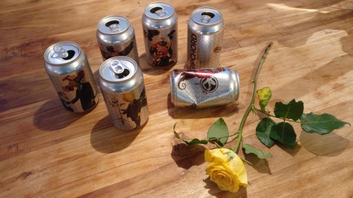 Empty BrewBoard cans and a yellow rose