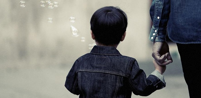 back of child's head as he walks away holding parent's hand. Bubbles in the air/ Credit: Life of Pix