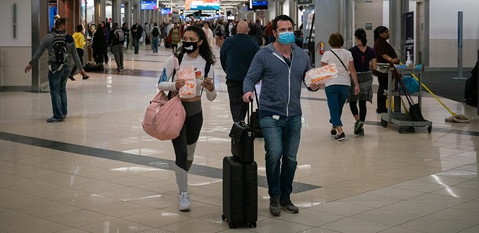People wearing masks hurry through a station concourse