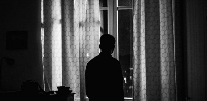 Silhouette of man standing at the window in a darkened room