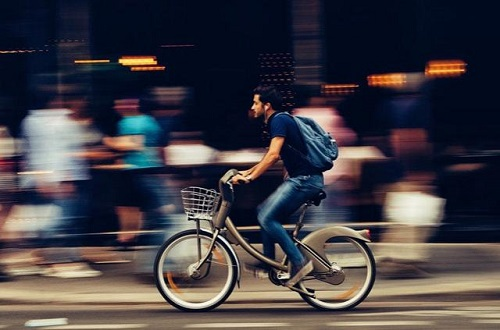 A side on photograph of a young adult male, in jeans and t-shirt, and with a blue backpack, cycling from camera right to camera left. The bike is silver-grey, with a basket on the front. The background is a busy city street, with pedestrians blurred in motion as the camera follows the cyclist.