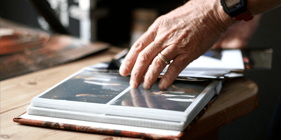A screenshot of hands over a book of photos, taken from an editing project