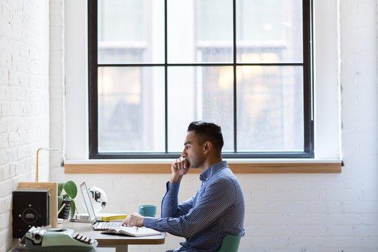 Man sitting at a desk looking at his laptop computer