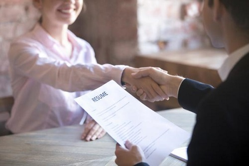 woman and man handshake as candidate hands over resume