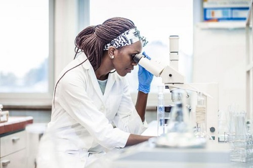 Female scientist working in a laboratory, using a Microscope