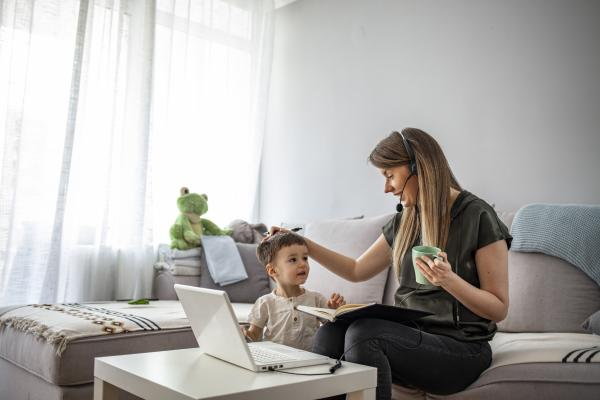 Mother working at home with laptop, headphones - and child