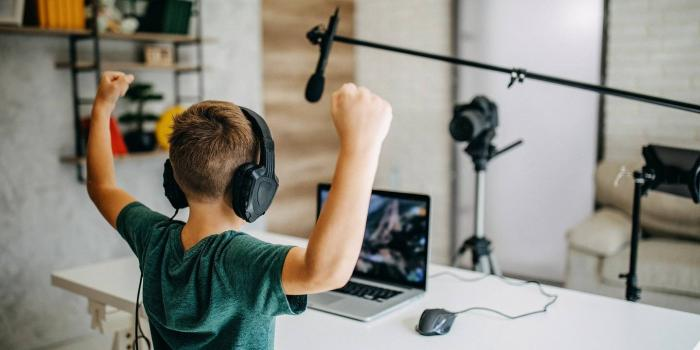 Child watching laptop and wearing headphones holds his arms above his head