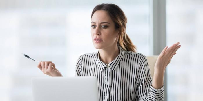 Frustrated woman looking at laptop with her hands in the air