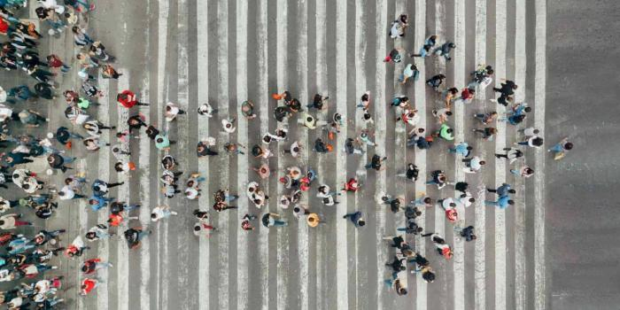 aerial view of people congregating to make the shape of an arrow